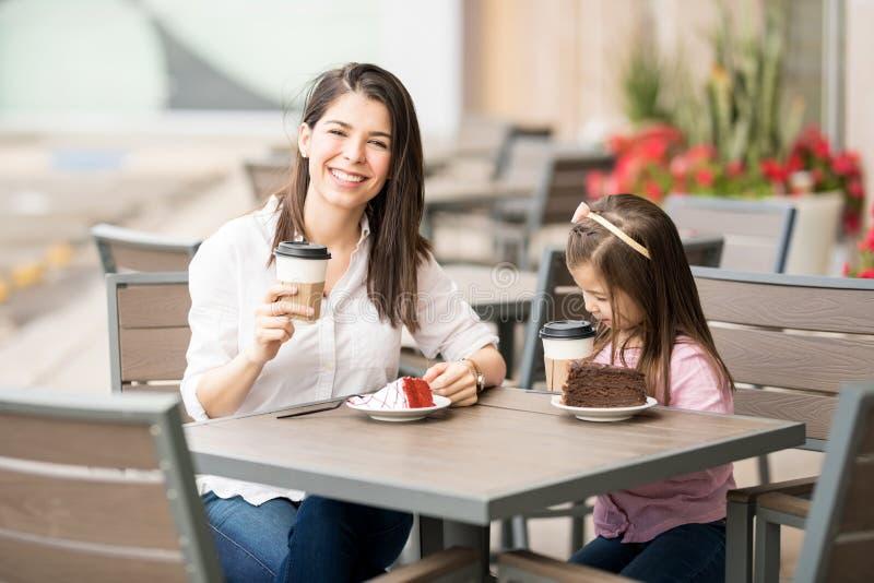 Morena latino-americano bonita com a filha no café foto de stock royalty free