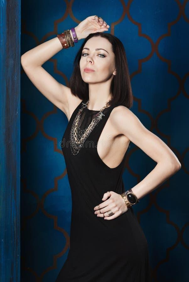 Morena lindo em um vestido de noite preto e em uma joia dourada luxuoso fotografia de stock royalty free