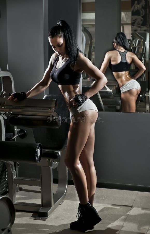 Morena lindo que levanta alguns pesos e que trabalha em seu bíceps em um gym Mulher da aptidão que faz o exercício Menina desport fotografia de stock