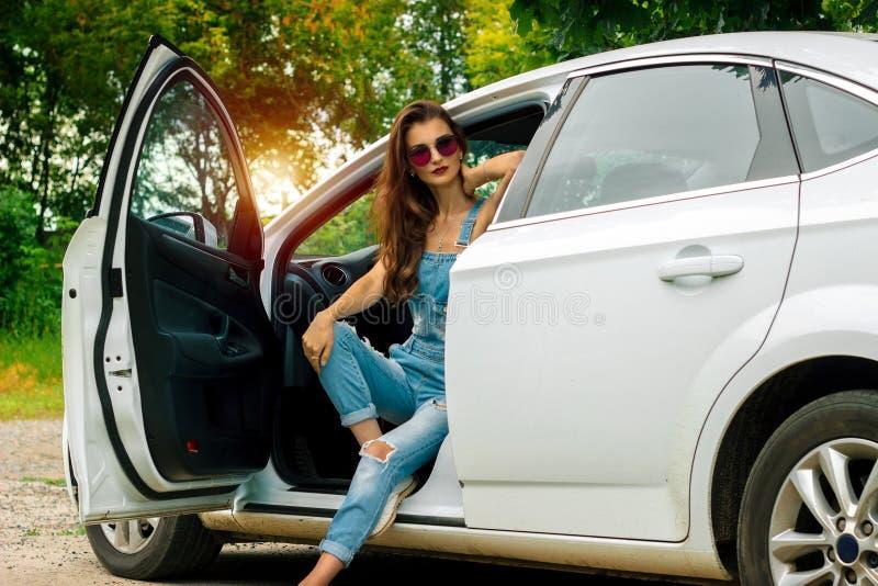 Morena lindo que levanta ao sentar-se em um carro foto de stock royalty free