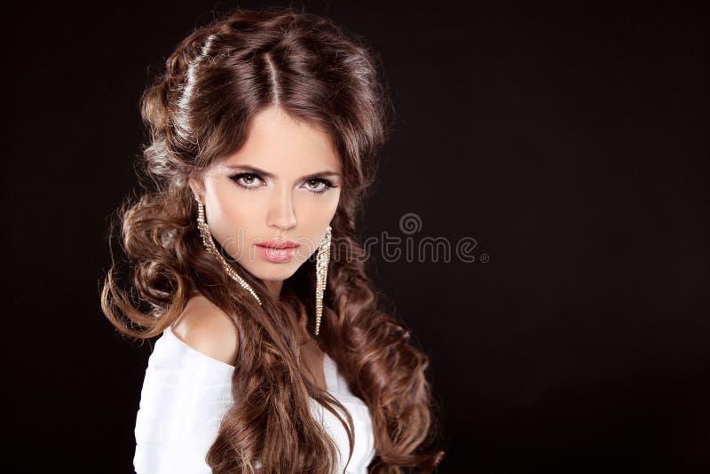 Morena. Mulher luxuosa com cabelo encaracolado longo de Brown. Modelo de forma imagem de stock royalty free