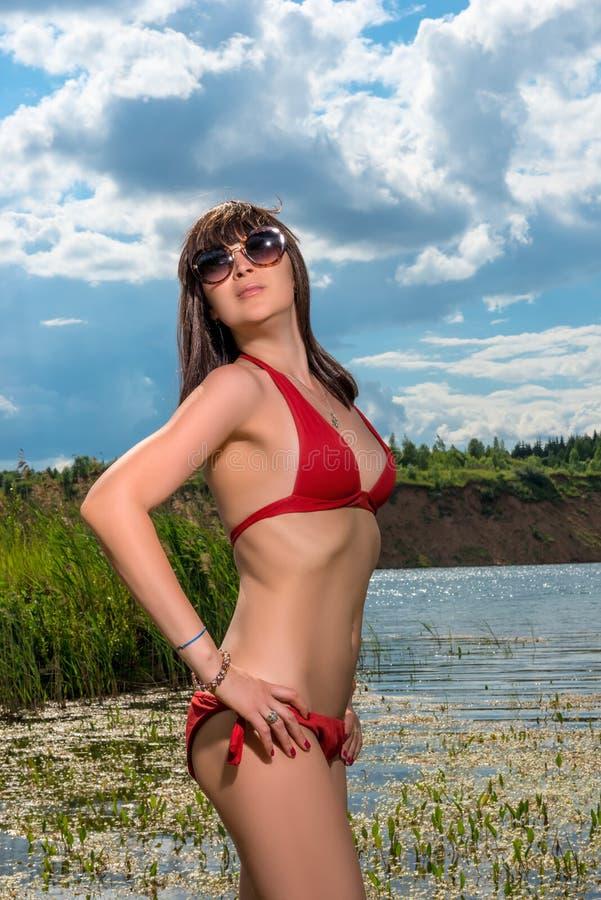 Morena no levantamento vermelho do roupa de banho fotos de stock royalty free