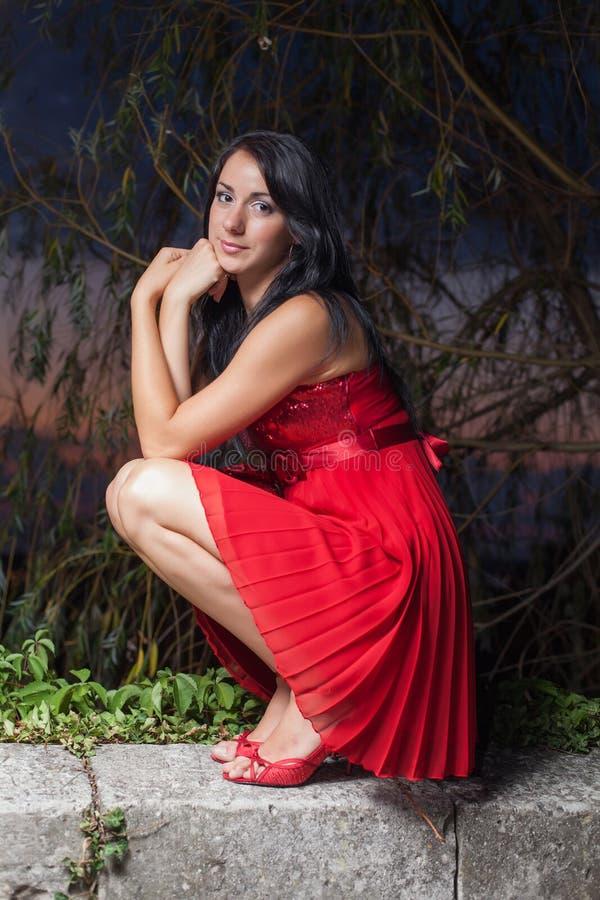 A morena nos sundress vermelhos que sentam-se sobre hunkers no parque da noite imagem de stock royalty free