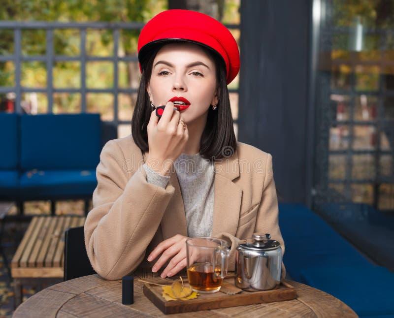 Morena nova bonita em um chapéu vermelho que pinta seus bordos com batom vermelho imagens de stock
