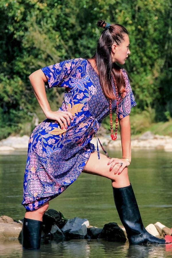 A morena nova bonita está estando em um rio da montanha fotografia de stock