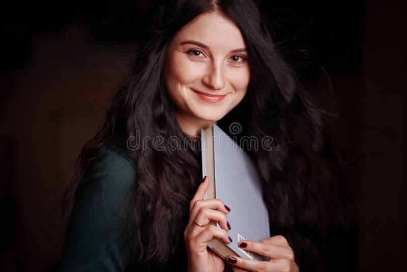 Morena nova bonita que levanta com um sorriso que guarda um livro em suas mãos imagens de stock