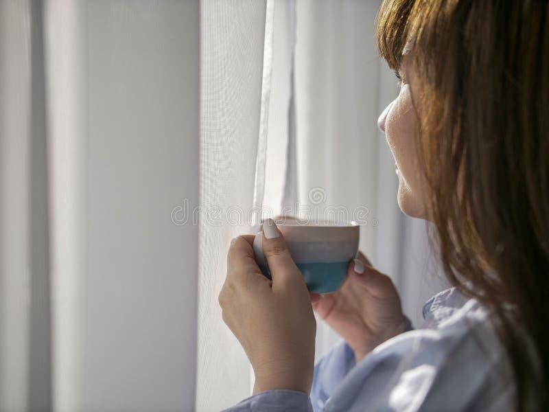 Morena nova com uma xícara de café pela janela, close-up fotos de stock