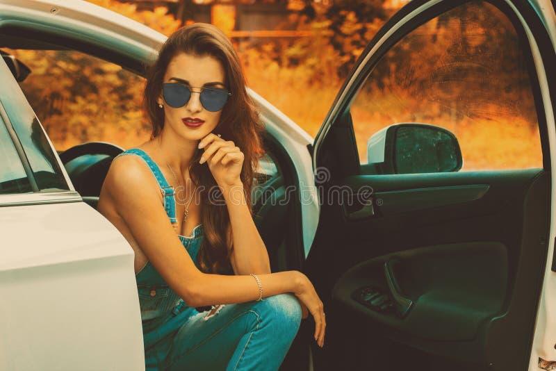 Morena nova em óculos de sol azuis no carro foto de stock