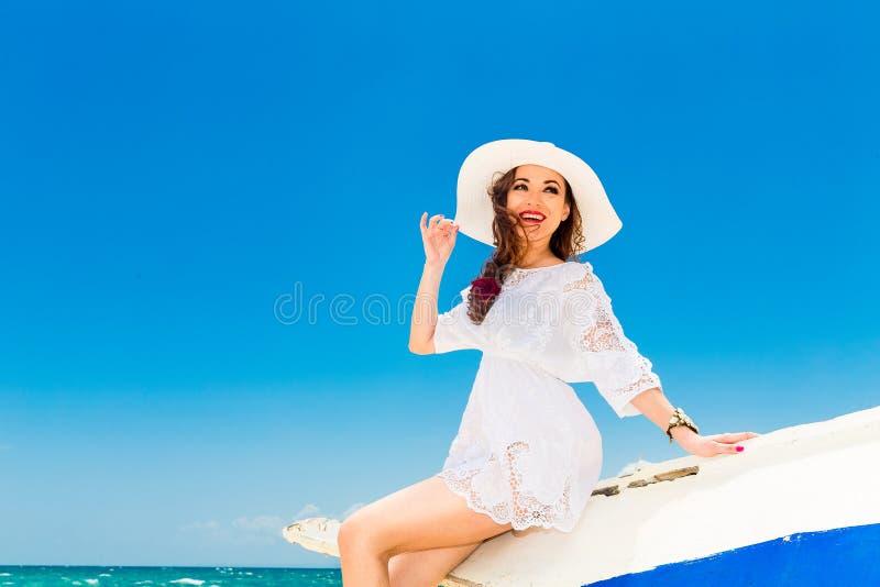A morena nova feliz em um chapéu de palha branco e o branco vestem o sittin imagens de stock