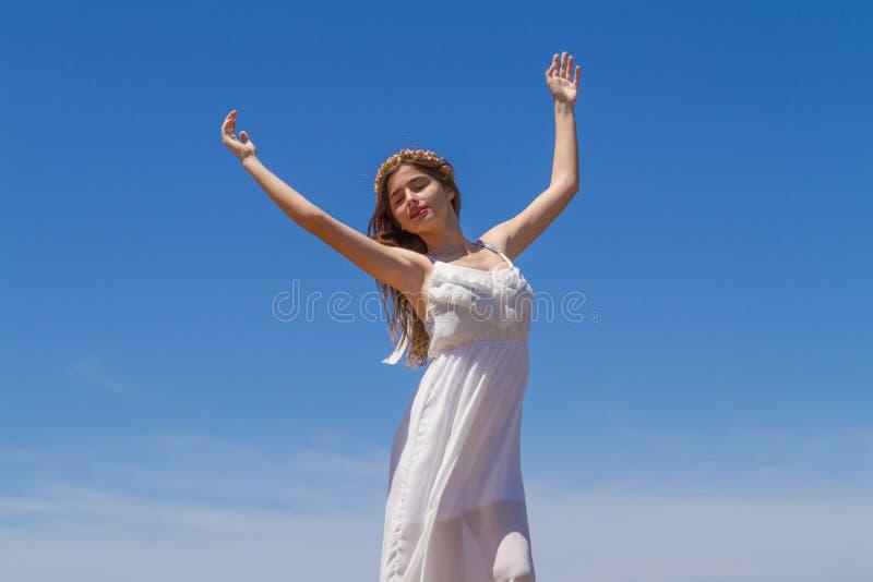 A morena nova no vestido frágil branco aprecia imagens de stock