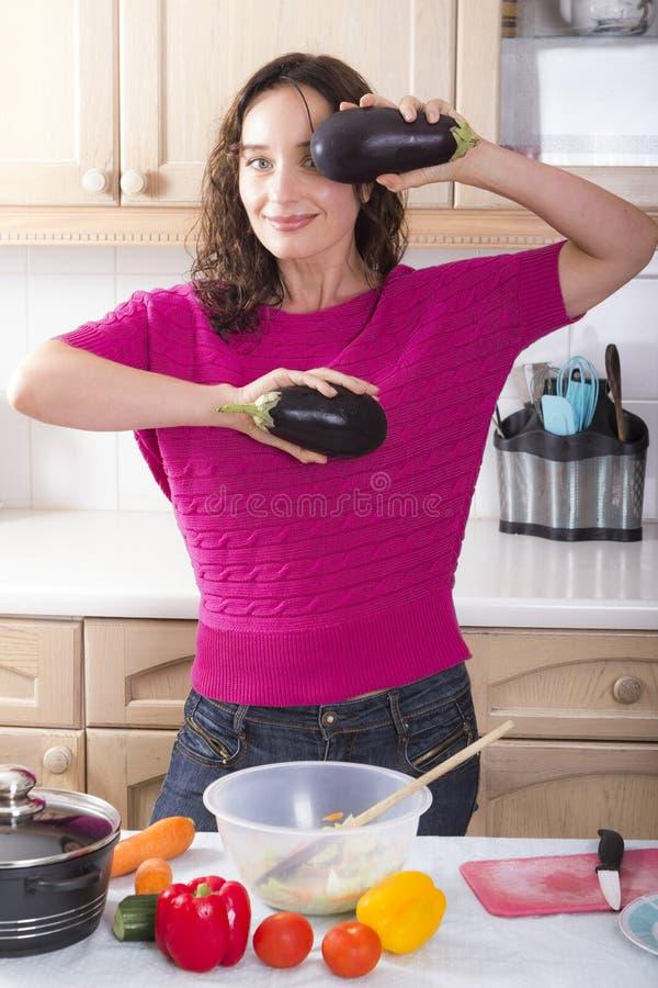 Morena nova que cozinha vegetais em casa fotos de stock royalty free