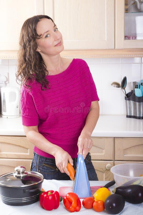 Morena nova que cozinha vegetais em casa imagens de stock