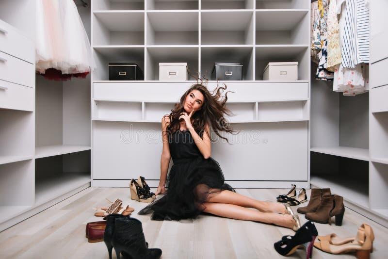 Morena nova que senta-se no assoalho e que pensa que vestir, sonhando sobre a roupa nova no vestuário luxary Sapatas foto de stock royalty free