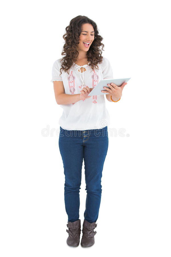 Morena ocasional alegre usando seu PC da tabuleta fotografia de stock