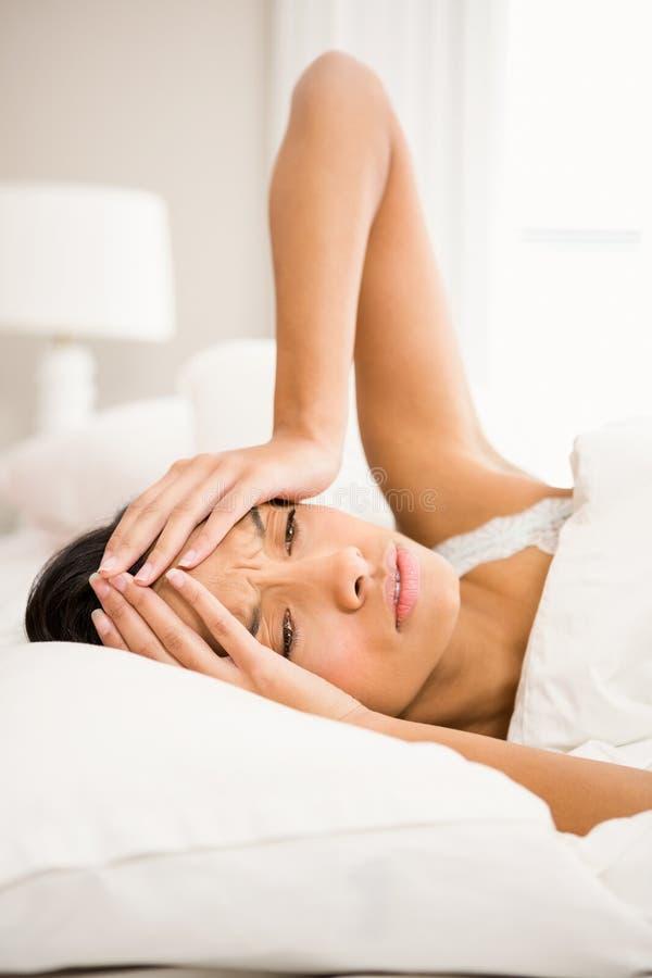 Morena olhando de sobrancelhas franzidas na cama foto de stock royalty free