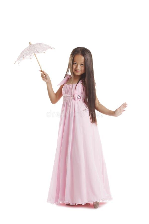 Morena pequena de cabelos compridos que levanta no vestido cor-de-rosa fotografia de stock royalty free