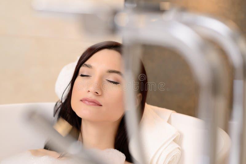 Morena que relaxa no banho com espuma Olhos fechados fotos de stock royalty free