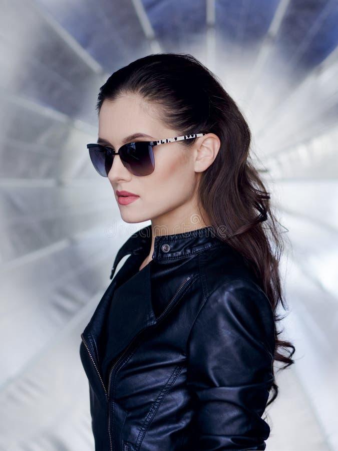Morena segura e 'sexy' com cara bonita, os óculos de sol à moda, o casaco de cabedal preto e penteado rebelde fotos de stock royalty free