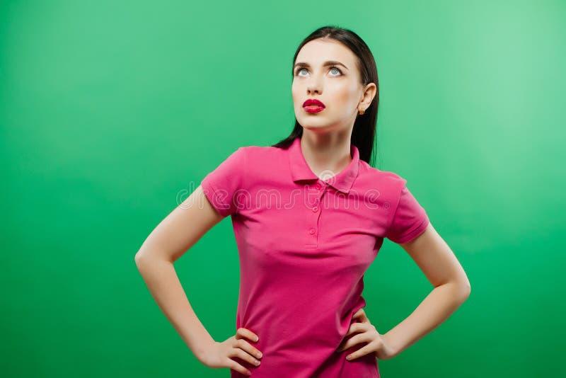 A morena sensual na camisa cor-de-rosa com composição brilhante está levantando no estúdio no fundo verde fotos de stock royalty free