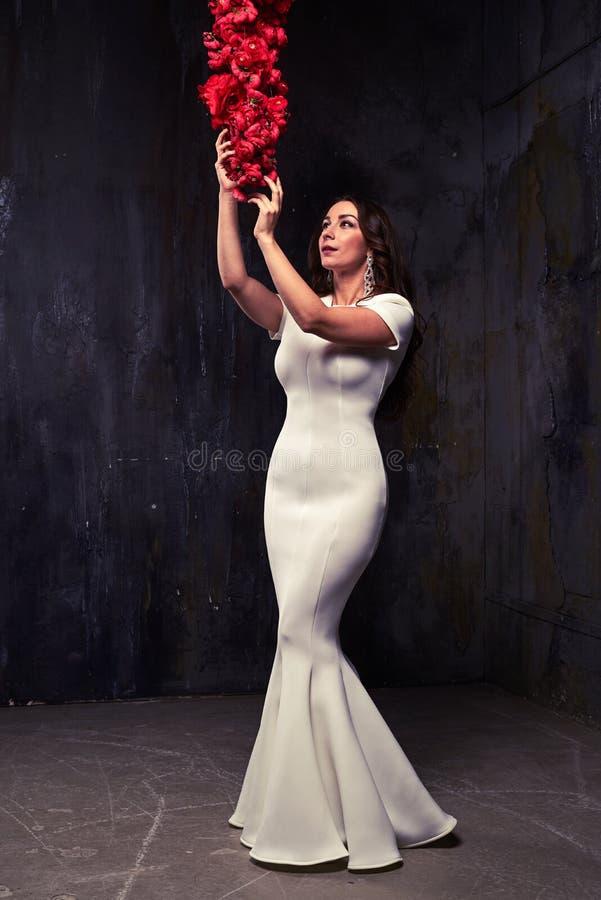 Morena sensual que toca em uns ganhos das rosas vermelhas isoladas sobre o blac fotografia de stock royalty free