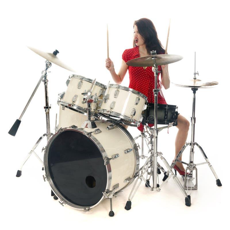 A morena 'sexy' no vestido vermelho joga o jogo do cilindro no estúdio foto de stock royalty free