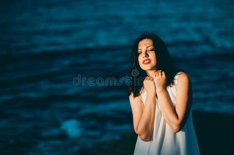Morena 'sexy' nova na água azul em um vestido branco na praia imagens de stock royalty free