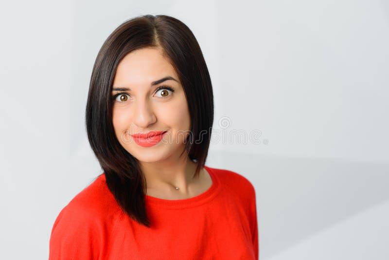 A morena surpreendeu o vermelho vestindo surpreendido da jovem mulher alegre foto de stock royalty free