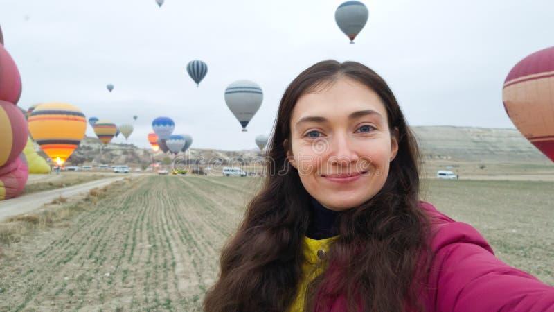 A morena toma um selfie no fundo dos balões crescentes no céu Amanhecer em Cappadocia Viajante feliz da menina fotos de stock royalty free