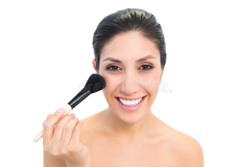 Morena usando uma escova e um sorriso do pó foto de stock