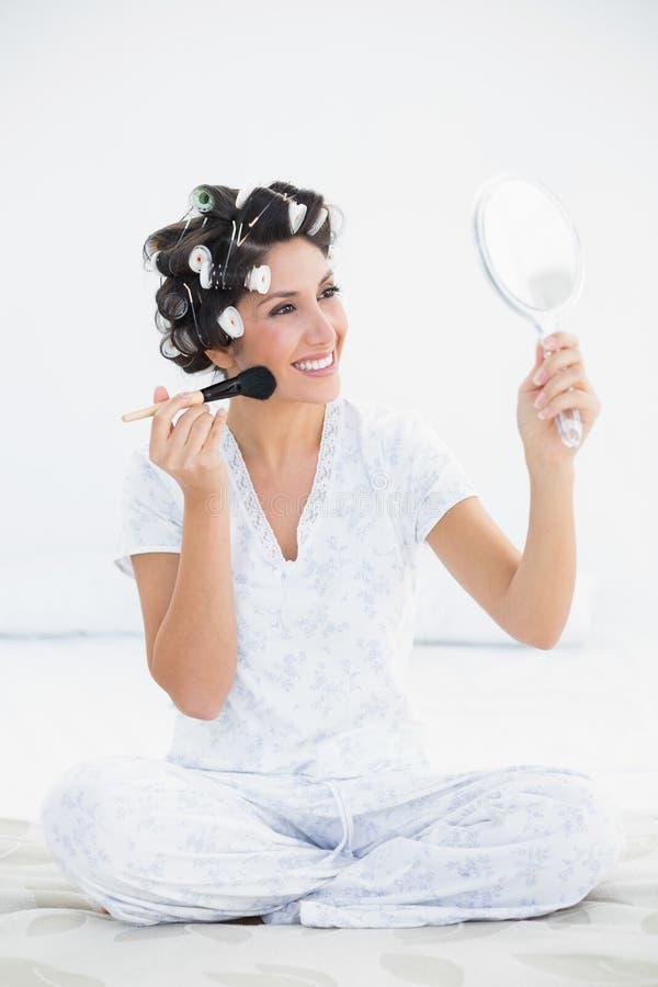 Morenita alegre en los rodillos del pelo que sostienen el espejo de mano y el applyi fotografía de archivo