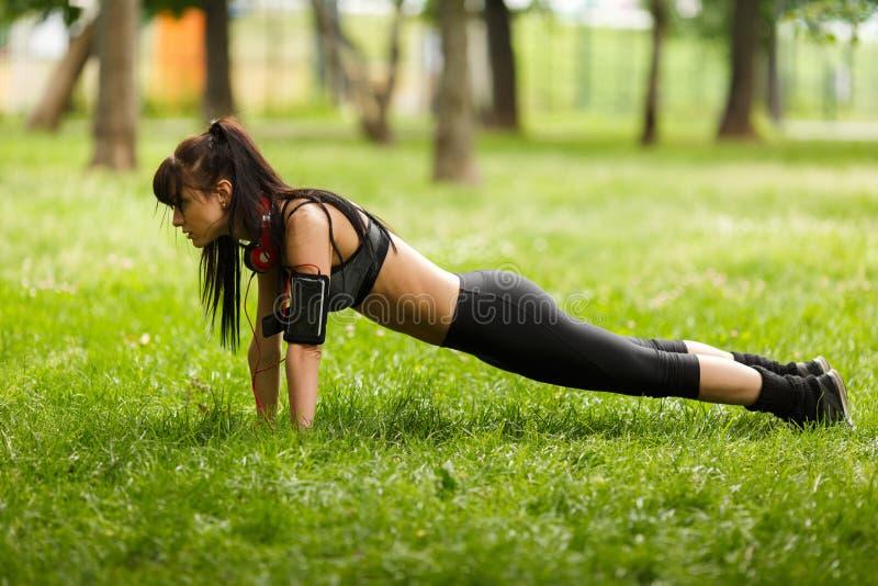 Morenita apta en los auriculares que hacen ejercicio de la base del tablón en hierba foto de archivo libre de regalías