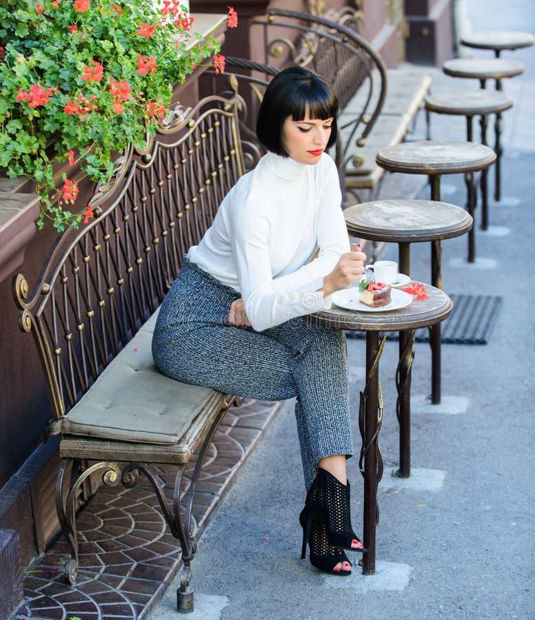 Morenita atractiva de la mujer comer el fondo gastrónomo de la terraza del café de la torta Disfrute gastronómico La muchacha rel foto de archivo libre de regalías