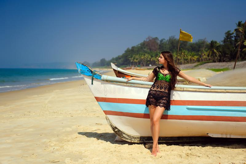 Morenita atractiva hermosa en la playa arenosa tropical cerca del barco de madera en fondo azul del mar y del cielo claro en día  foto de archivo