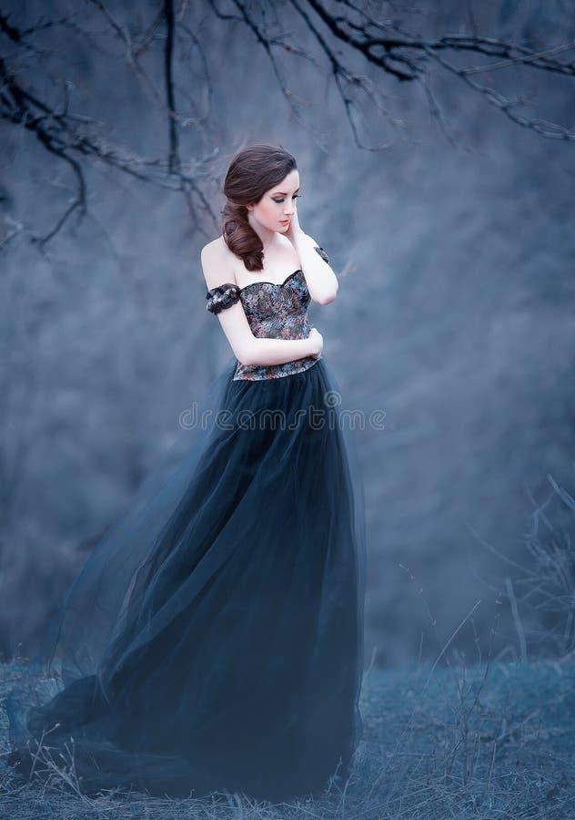 Morenita atractiva magnífica, señora en un vestido negro largo con los brazos y los hombros abiertos desnudos, la muchacha solame imágenes de archivo libres de regalías