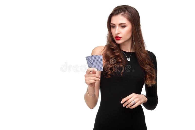 Morenita atractiva que presenta con dos tarjetas de los as en sus manos, aislamiento del pelo rizado del concepto del póker en el fotos de archivo