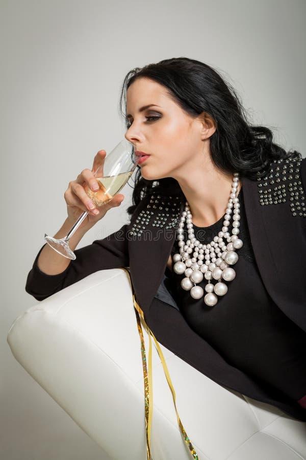 Morenita atractiva que sostiene un vidrio de champán imagen de archivo libre de regalías