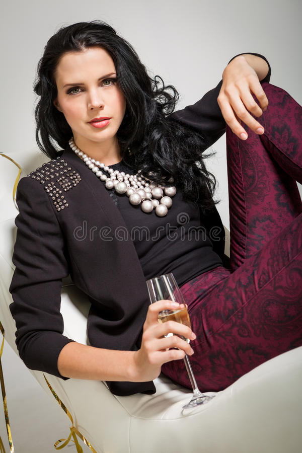 Morenita atractiva que sostiene un vidrio de champán foto de archivo