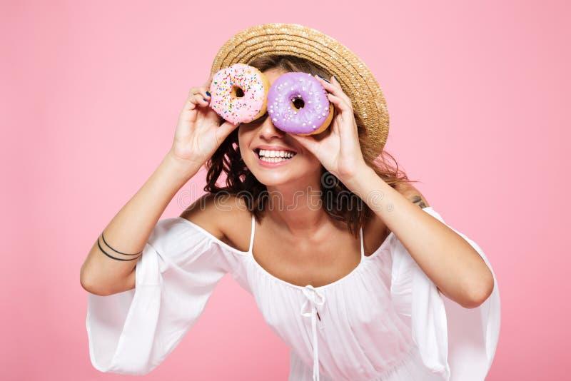 Morenita bastante joven en el sombrero de paja que sonríe y que mira con d foto de archivo