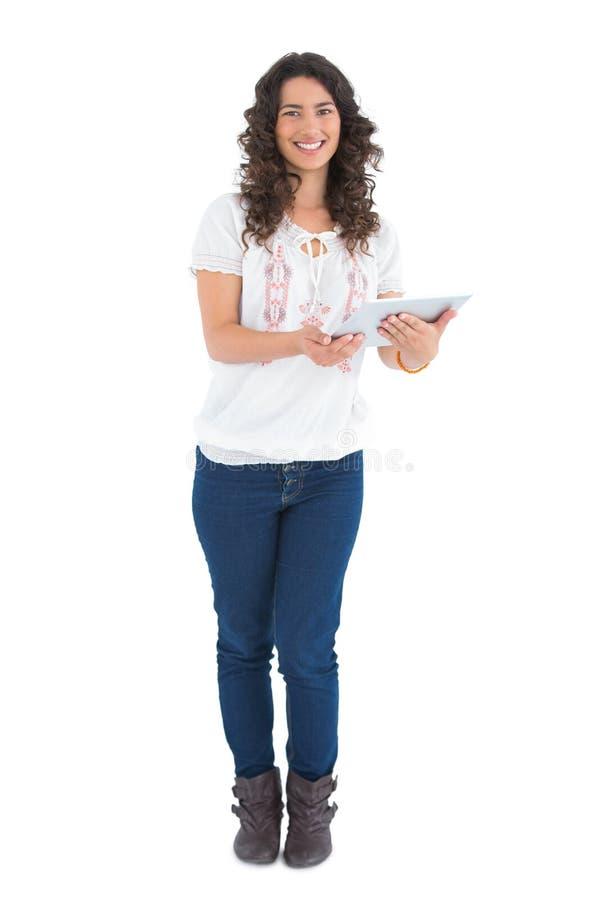 Morenita casual sonriente usando su PC de la tableta foto de archivo libre de regalías
