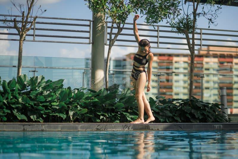 Morenita caucásica delgada atractiva que camina entre los arbustos y los árboles verdes en el borde de la piscina en tejado con e fotos de archivo