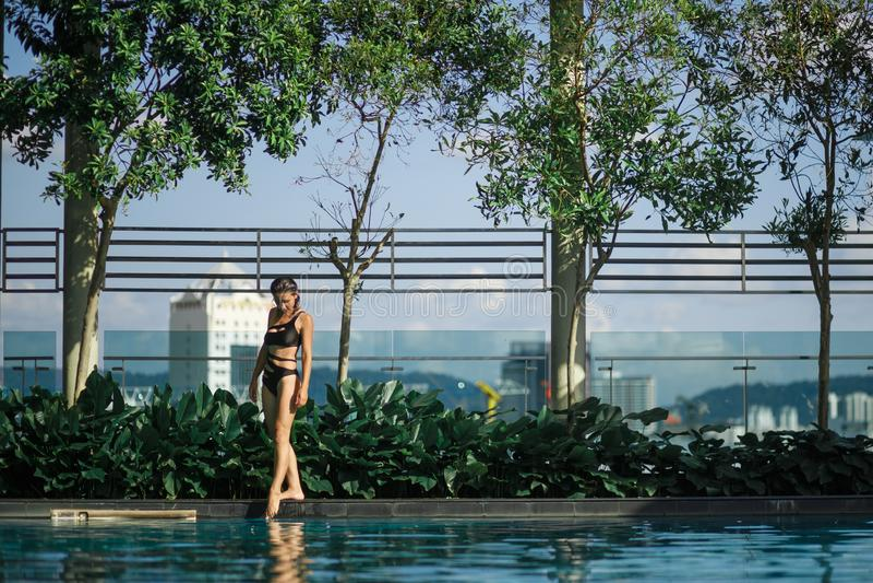 Morenita caucásica delgada atractiva que camina entre los arbustos y los árboles verdes en el borde de la piscina en tejado con p fotos de archivo libres de regalías