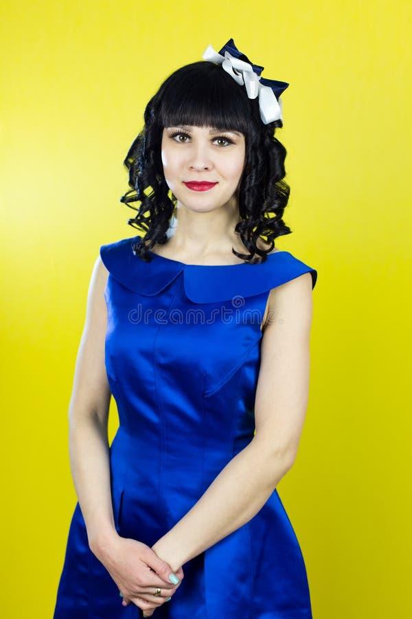 Morenita de la muchacha en un vestido azul en un fondo amarillo imagen de archivo