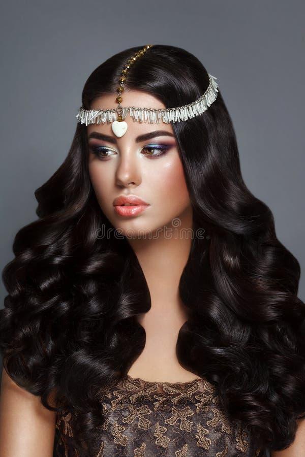 Morenita de la mujer de la belleza del encanto con el pelo rizado perfecto gourgeous brillante hermoso y el maquillaje imagen de archivo libre de regalías