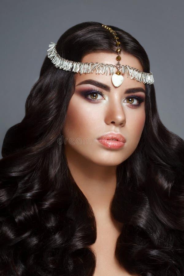 Morenita de la mujer de la belleza del encanto con el pelo rizado perfecto gourgeous brillante hermoso y el maquillaje imágenes de archivo libres de regalías