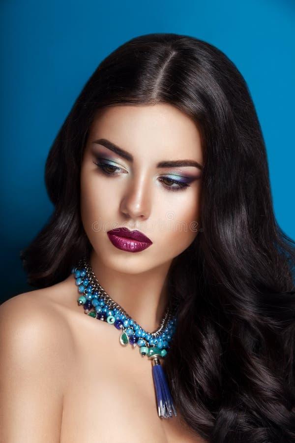 Morenita de la mujer de la belleza del encanto con el pelo rizado perfecto gourgeous brillante hermoso y el maquillaje imagenes de archivo