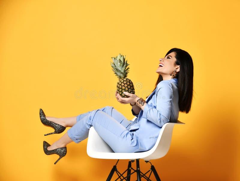 Morenita de risa de la mujer de negocios en el pantsuit que se sienta en la butaca de lado que sostiene la piña en sus palmas abi fotos de archivo libres de regalías