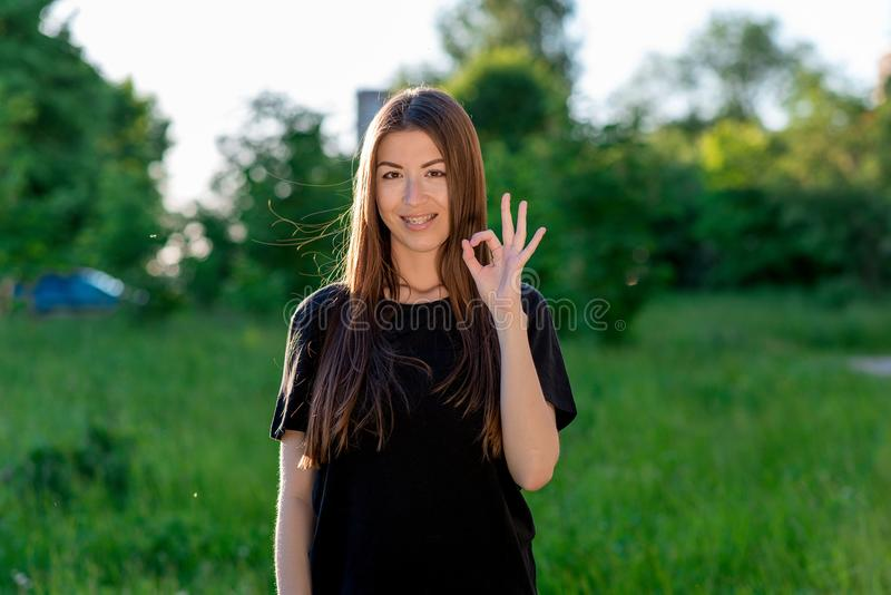 Morenita del asiático de la chica joven En el verano en el aire abierto Una mano muestra MUY BIEN con sus fingeres Positivo emoci imágenes de archivo libres de regalías