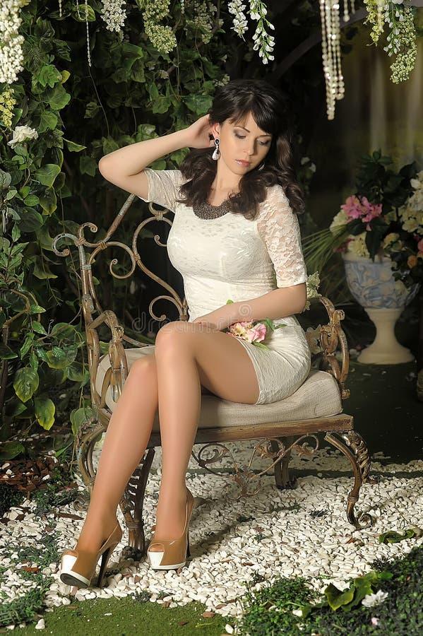 Morenita delgada en un vestido blanco en el jardín imagen de archivo