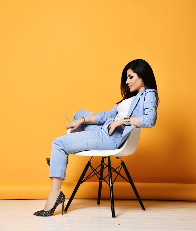 Morenita elegante de la mujer de negocios en traje oficial azul y los zapatos de tacón alto que se sientan en la butaca del diseñ foto de archivo libre de regalías
