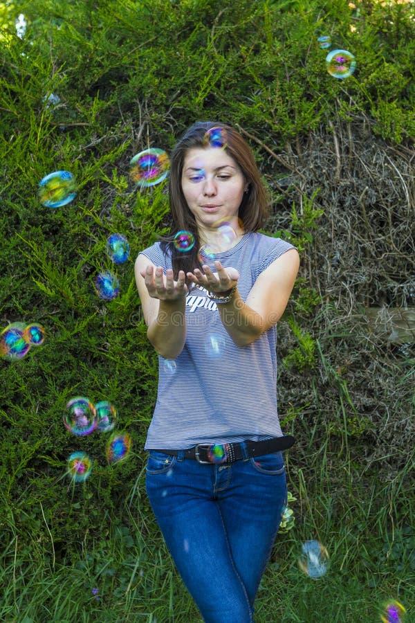 Morenita encantadora con las burbujas al aire libre imagenes de archivo